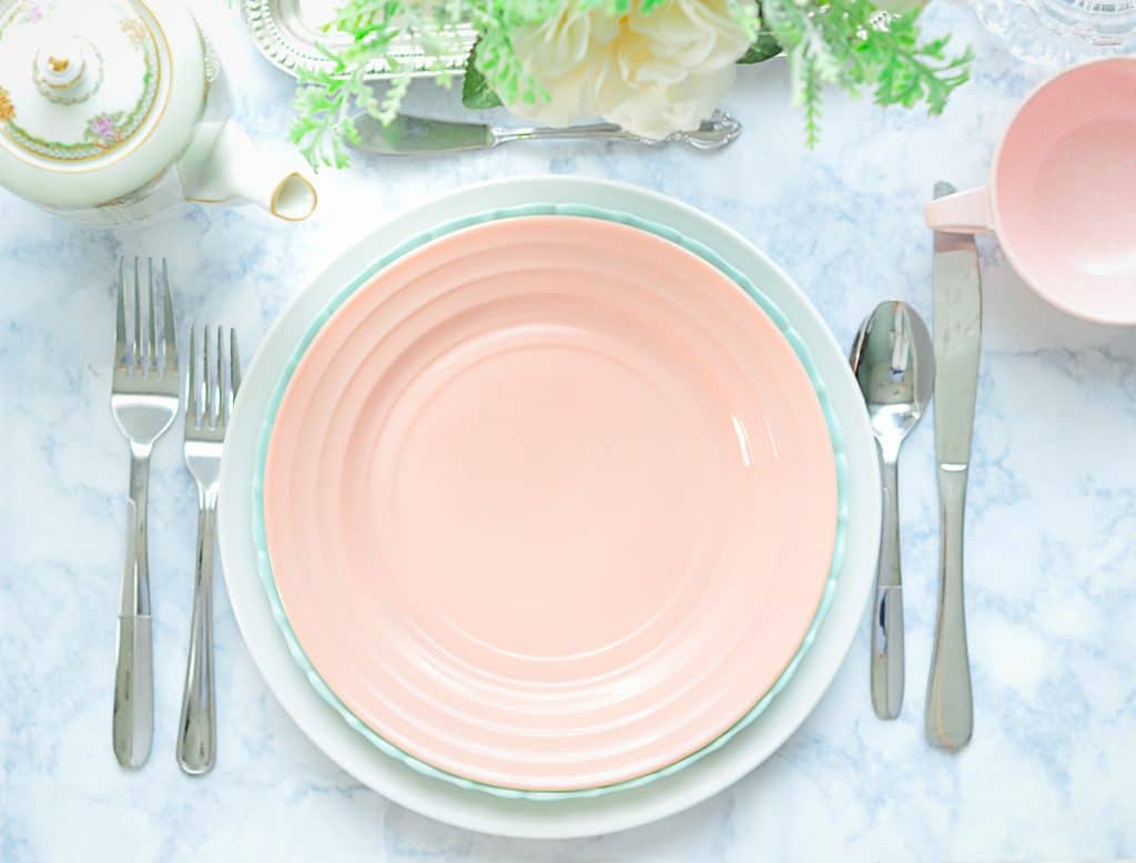 Vintage Pastel Dinnerware table setting with silverware and flower arrangement.