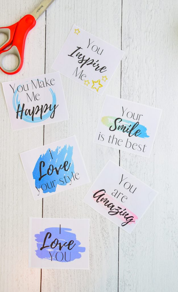 """Square free compliment card printable  reading """"You make me happy"""", """"your smile is the best"""" and """"I love your style"""" on a white wooden table laying next to a pair of scissors."""